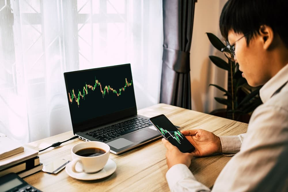 Asian young man looking at stock graphs cryptocurrency using Bitcoin Code trading platforms on smartphone and laptop.